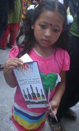 Child at fair in Nepal holding CEPHED lead paint flyer