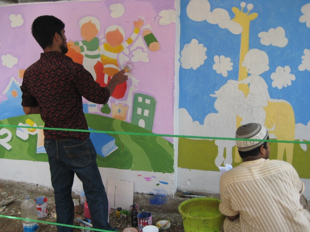 Men painting a mural in Bangladesh