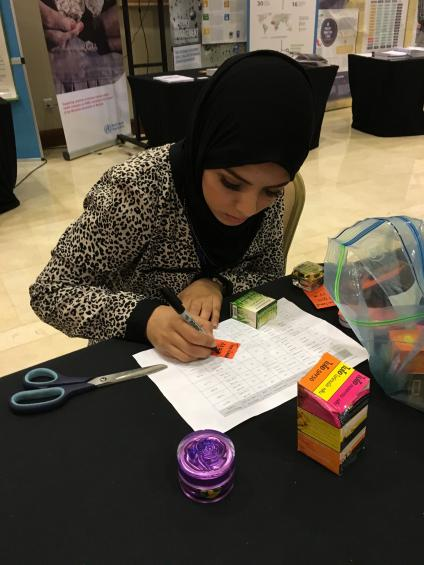 Nour Labidi preparing some of the cosmetics that contain mercury for display at the IPEN booth
