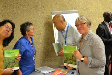 Rossana Dewi (Gita Pertiwi) and Stephanie Williamson (PAN UK) holding copies of PAN's new agroecology book, while Meriel Watts speaks with an event attendee in the background