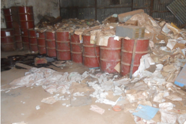 Drums of obsolete pesticides stored in the MOFACU warehouse with documents scattered on the floor